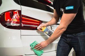 seseorang menggunakan cairan waterless car wash untuk mencuci mobil